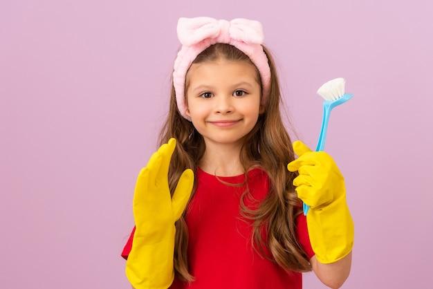 Uma menina com uma camiseta vermelha e luvas de borracha está segurando uma escova de limpeza.
