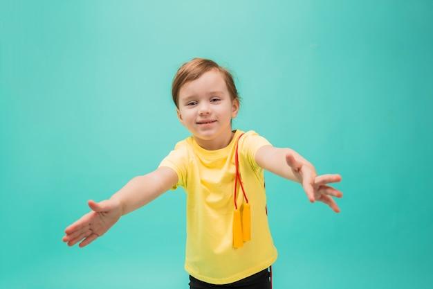 Uma menina com uma corda de pular estendeu os braços para o lado contra um espaço turquesa. garota feliz com um rabo de cavalo em uma camiseta amarela para um estilo de vida saudável.