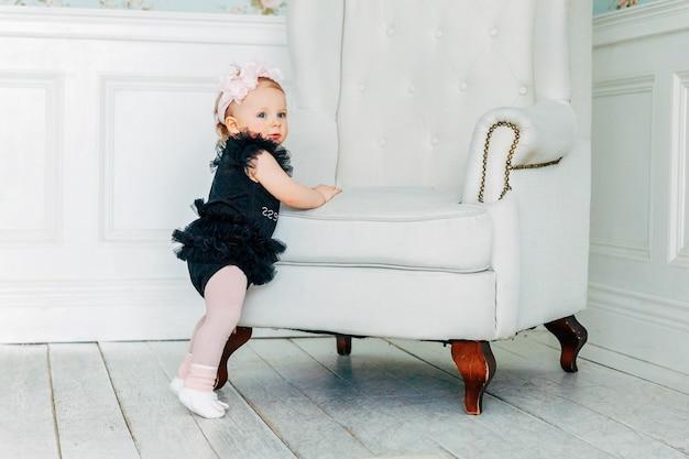 Uma menina com uma coroa de flores de primavera em pé perto de uma cadeira confortável na sala de estar iluminada