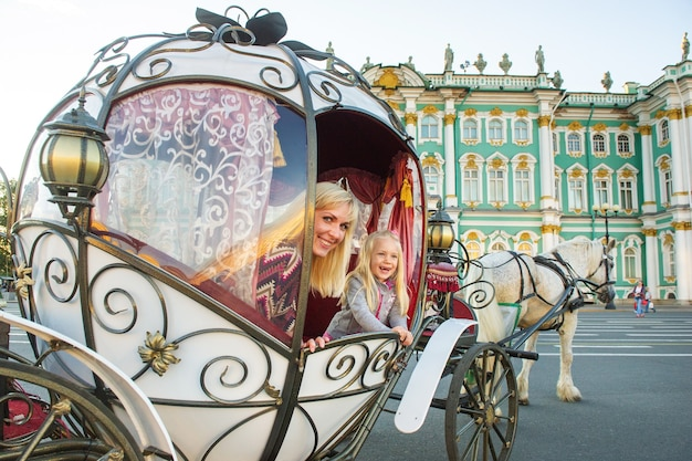 Uma menina com uma criança em uma carruagem velha na praça do palácio em são petersburgo