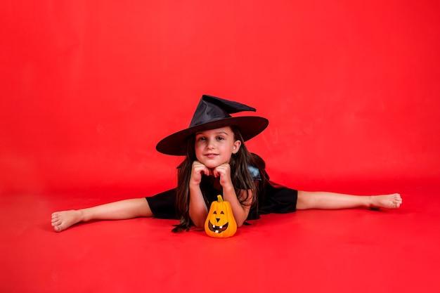 Uma menina com uma fantasia de bruxa e um chapéu está sentada em um cordão com uma abóbora em um fundo vermelho com uma cópia do espaço