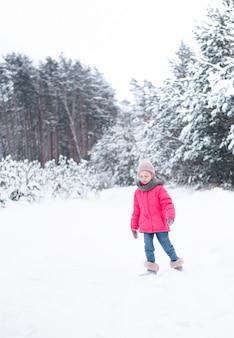 Uma menina com uma jaqueta brilhante joga na floresta de inverno nevado.