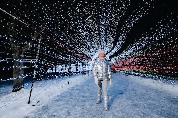 Uma menina com uma jaqueta prateada no inverno com luzes acesas à noite em uma rua decorada de natal