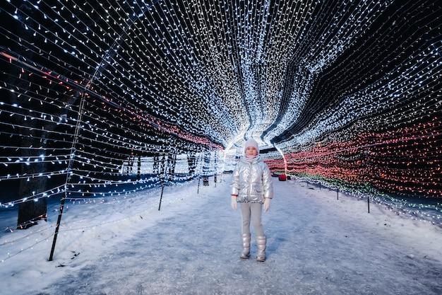 Uma menina com uma jaqueta prateada no inverno com luzes acesas à noite em uma rua decorada de natal.