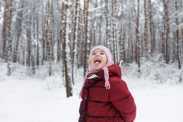 Uma menina com uma jaqueta vermelha está em uma floresta coberta de neve, pegando flocos de neve com a língua.