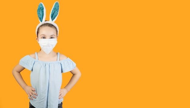 Uma menina com uma máscara médica de coronavírus no rosto, na cabeça com orelhas de coelho, mãos na cintura