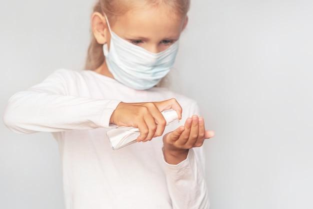Uma menina com uma máscara médica desinfeta as mãos com um agente antibacteriano em um fundo isolado