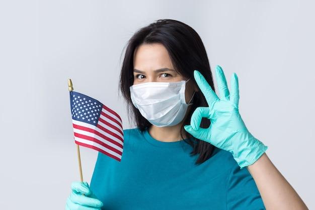 Uma menina com uma máscara médica e luvas segura uma bandeira americana nas mãos. conceito de coronavirus