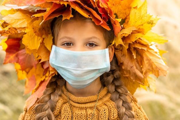 Uma menina com uma máscara médica no rosto.
