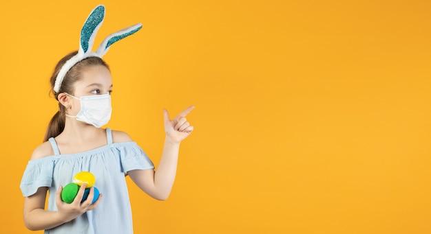Uma menina com uma máscara médica para coronavírus no rosto, na cabeça com orelhas de coelho, segura ovos de páscoa nas mãos e aponta para um espaço vazio para texto com o dedo