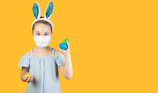 Uma menina com uma máscara médica para coronavírus no rosto, na cabeça com orelhas de coelho, segura ovos de páscoa nas mãos
