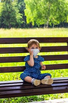 Uma menina com uma máscara médica sentada sozinha em um banco em um parque de verão