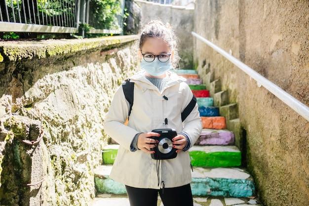 Uma menina com uma máscara vai passear com uma câmera fotográfica com escadas coloridas