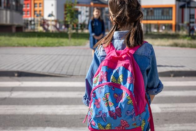 Uma menina com uma mochila vai para a escola, volta para a escola.