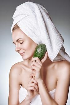 Uma menina com uma pele saudável e bonita segura um abacate perto do rosto