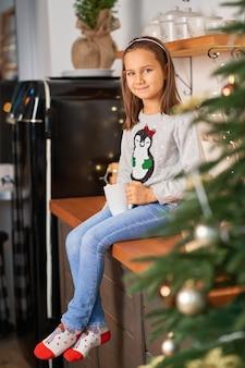 Uma menina com uma xícara de chá quente sonha com um presente de natal do papai noel