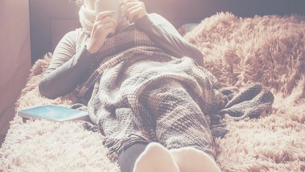 Uma menina com uma xícara de naya encontra-se debaixo de um cobertor. foco seletivo.