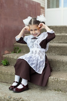 Uma menina com uniforme escolar brinca com brinquedos