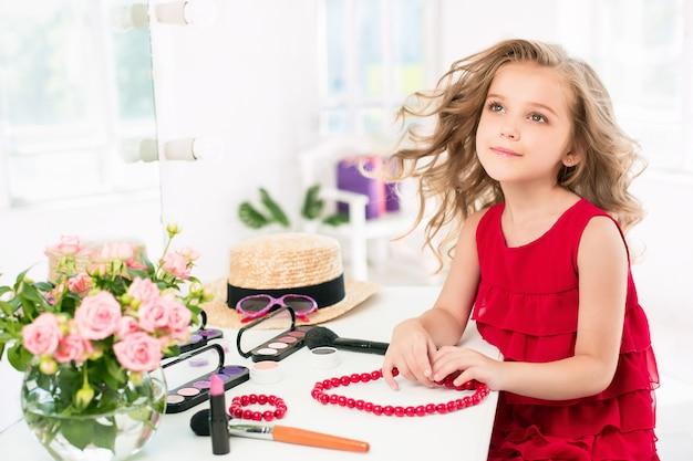 Uma menina com vestido vermelho e cosméticos.