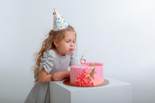 Uma menina comemora seu aniversário soprando as velas de um bolo