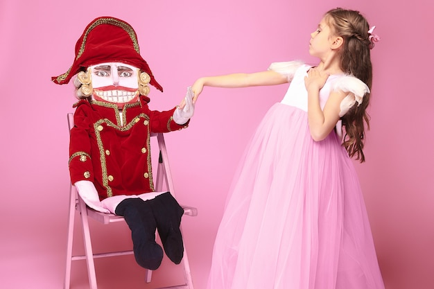 Uma menina como bailarina de beleza no vestido longo rosa com quebra-nozes no estúdio rosa