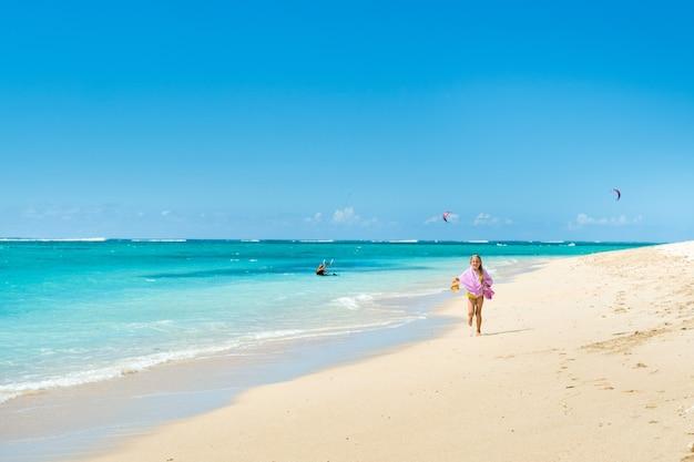 Uma menina corre ao longo da praia da ilha tropical de maurício, no oceano índico.
