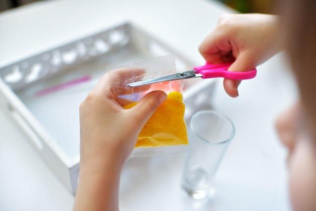Uma menina corta com uma tesoura um saco de veludo que faz uma vela com pequenos grânulos de parafina