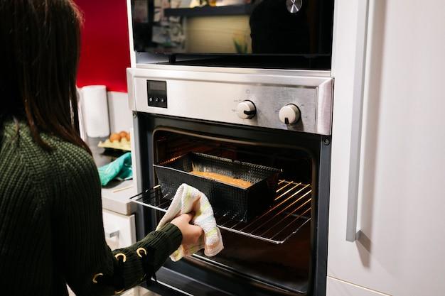 Uma menina cozinha um pão de ló no forno em sua cozinha em casa