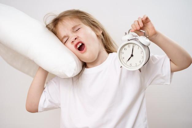 Uma menina criança bocejando abraça um travesseiro e um despertador em um fundo branco. ascensão precoce das crianças à escola e ao jardim de infância. roupa de cama confortável.