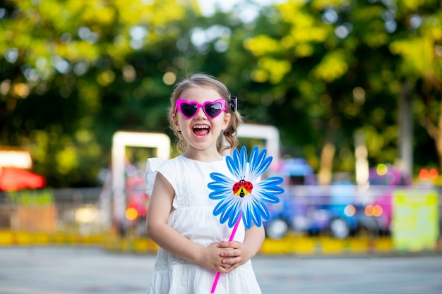 Uma menina criança feliz sorri ou ri em um parque de diversões com uma plataforma giratória na mão e óculos cor de rosa no verão