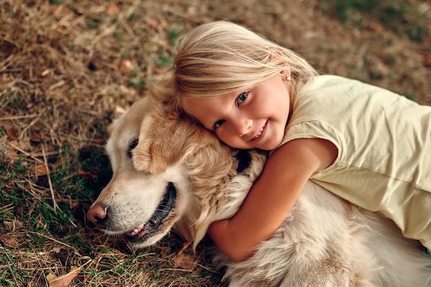 Uma menina criança loira fofa encontra-se na grama, abraçando seu amigo, um cão labrador.