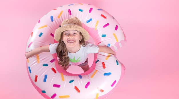 Uma menina criança no vestuário desportivo, deitada em um círculo inflável donut. fundo rosa. vista do topo. conceito de verão.