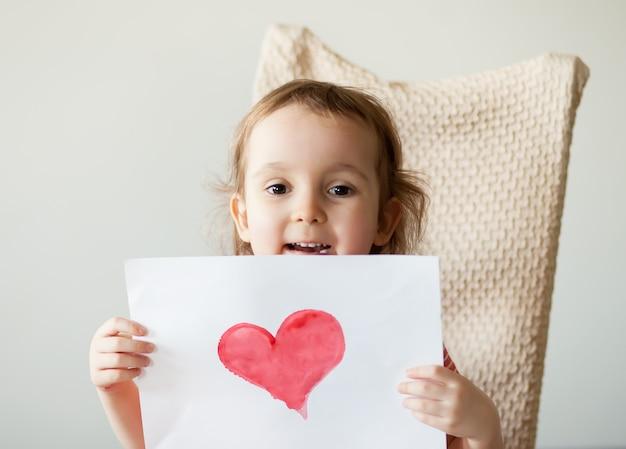 Uma menina criança segurando uma folha com um coração vermelho pintado