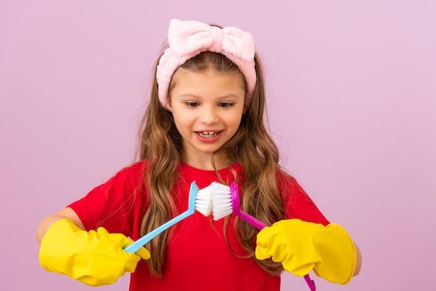Uma menina cuida da limpeza da casa. limpa sua casa. luvas de borracha e escovas de limpeza.