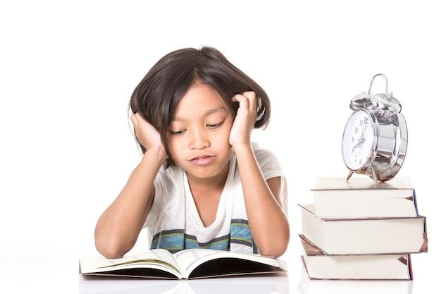 Uma menina da escola adolescente estuda muito sobre o livro em casa quando ele abaixa a cabeça com o braço