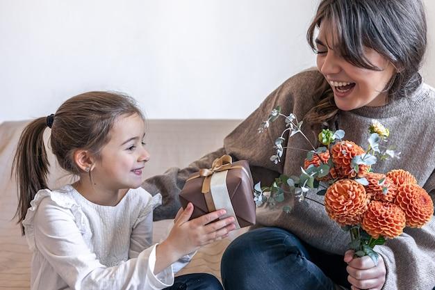 Uma menina dá um presente e um buquê de flores para a mãe
