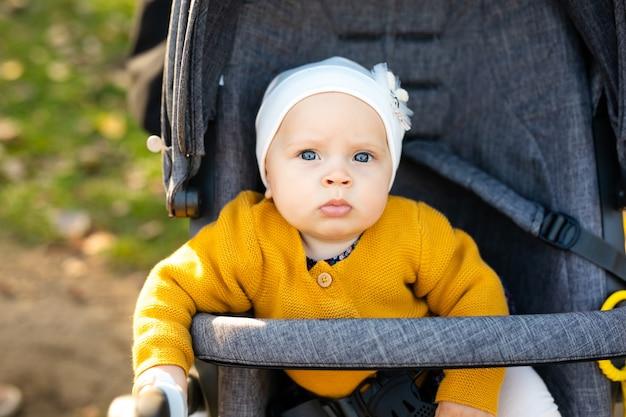 Uma menina de 1 ano vestida com uma camisa amarela e um chapéu branco está sentada em um carrinho cinza no parque