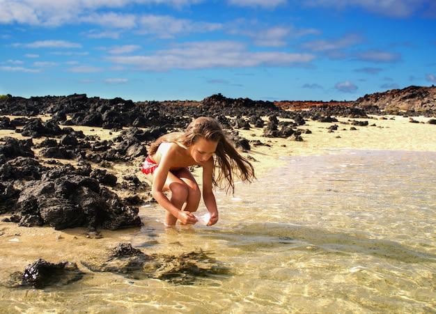 Uma menina de 10 anos pescando peixes e caranguejos, na água à beira-mar, oceano