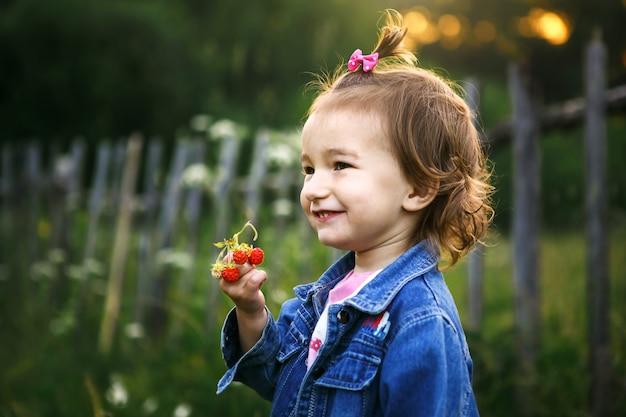 Uma menina de 2 anos na aldeia segura um morango maduro nas mãos e sorri maliciosamente. vitaminas, horário de verão. dia internacional da criança. natureza ao ar livre