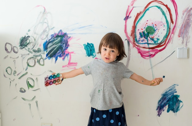 Uma menina de 3 anos pintou um olhar arqueado com tinta e um pincel na parede do quarto.
