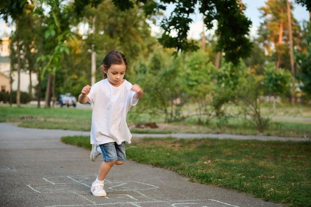 Uma menina de 4 anos, esportiva e ativa, joga amarelinha, se revezando para saltar sobre os quadrados marcados no chão. jogos infantis de rua em clássicos.