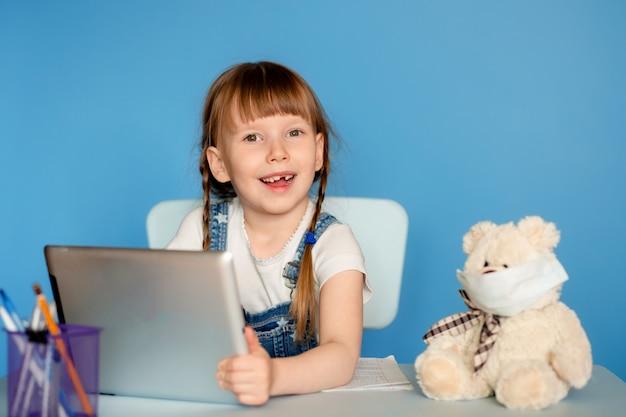 Uma menina de 5 a 6 anos sentada à mesa executa tarefas remotas de lição de casa sobre o tablet. isolar em uma parede azul.
