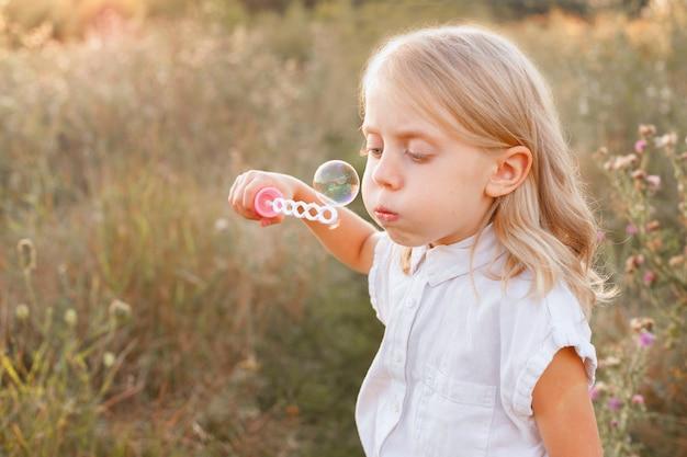 Uma menina de 5 anos infla bolhas de sabão em uma caminhada no fim de semana. proteção infantil