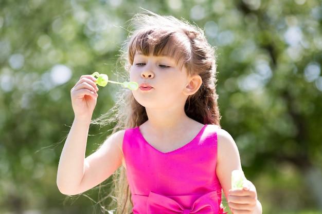 Uma menina de 5 anos solta bolhas de sabão.