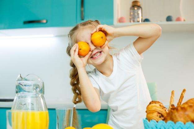 Uma menina de 7 a 8 anos está sentada na cozinha e faz os olhos com uma tangerina.