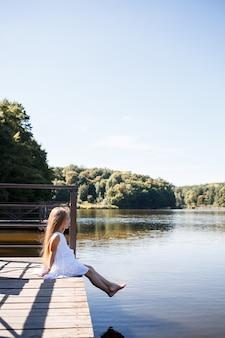 Uma menina de 7 anos com longos cabelos loiros à beira do lago está sentada em uma bolsa com as pernas na água. ela espirra os pés no lago. menina descalça em um vestido branco com cabelo comprido.