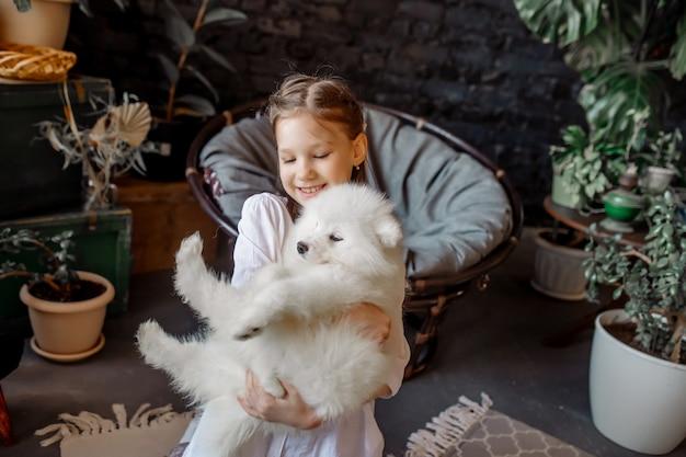 Uma menina de 8 anos brinca com um animal de estimação - um cachorrinho branco e fofo em casa