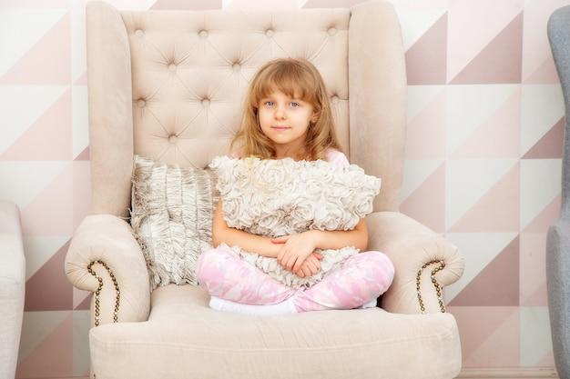 Uma menina de aparência caucasiana está sentada em uma poltrona com um travesseiro em uma sala bem iluminada em estilo escandinavo