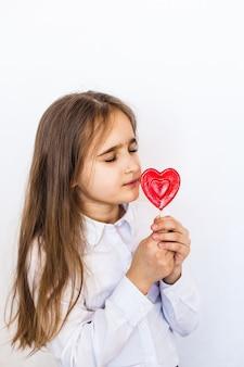 Uma menina de aparência europeia em um fundo branco tem um pirulito em forma de coração na mão, amor, presente, família, dia dos namorados