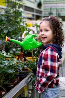 Uma menina de cabelos cacheados rega as plantas da casa